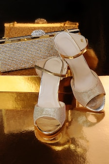 Couple of gold shoes on a gold background close-up