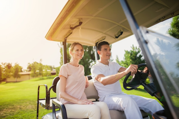 Couple in a golf cart people going to play golf.
