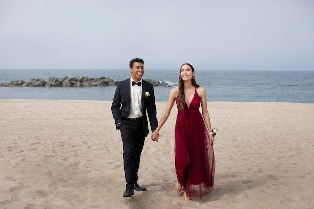 Couple in graduation prom clothing at the beach