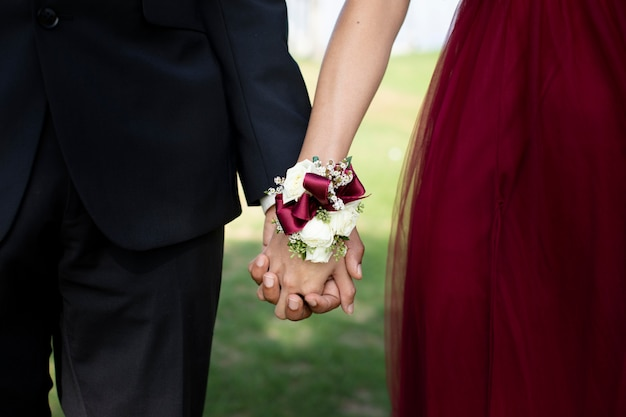 Couple in graduation prom clothing holding hands