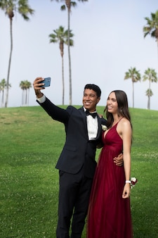 Couple in graduation prom clothing taking a selfie