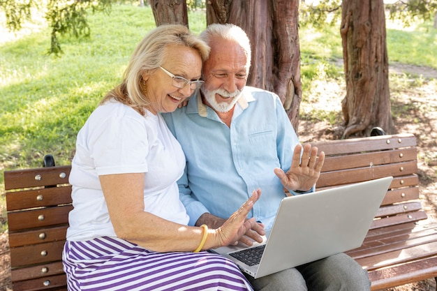 Couple greeting someone on laptop