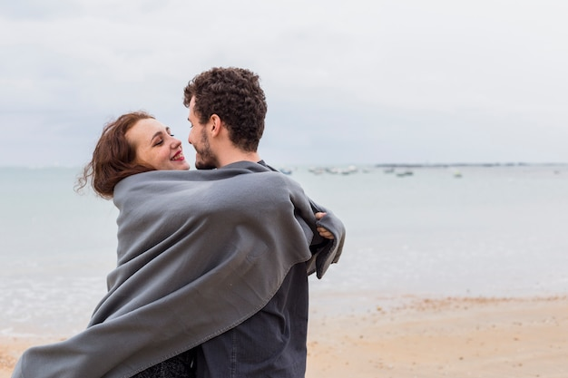 Couple in grey blanket hugging on sea shore
