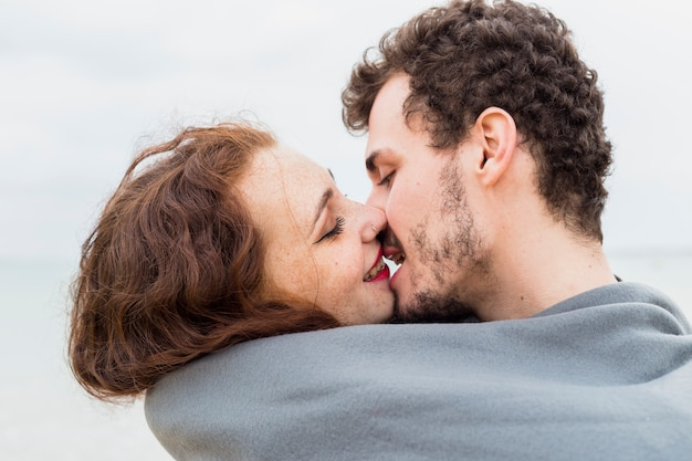 Couple in grey blanket kissing