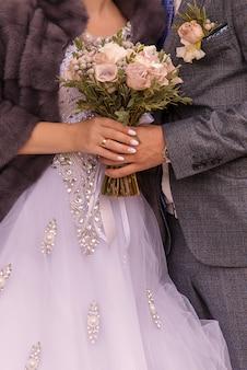 カップルの新郎と新婦の花束とクローズアップの手