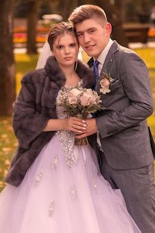 公園を歩いて結婚式の日に一緒にカップルの新郎と新婦