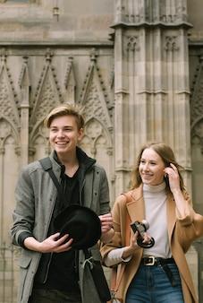Couple, guy and girl smiling near landmarks
