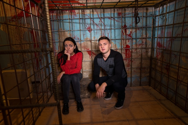 Couple of halloween victims imprisoned in a metal cage with a blood splattered wall behind them sitting in terror awaiting their fate