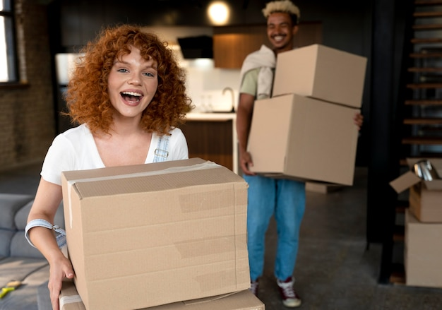 Couple handling cardboard boxes with belongings after moving together in new home
