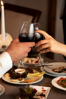 Couple hands cheering red wine glasses at dinner