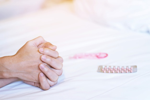 Couple hands of lovers on bed while having activity time, blurred condom and birth control pills pack