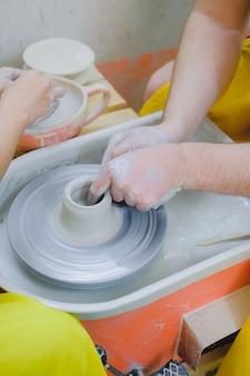 Пара рук, работающих с глиной на гончарном круге. творческая романтическая идея свидания