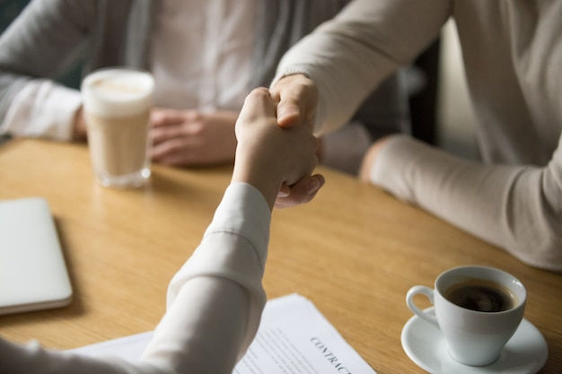 Couple handshaking businesswoman making deal in cafe, close up view