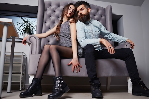 Couple of handsome bearded hipster in jeans shirt and pretty cute young fashion girl or woman sitting on couch.