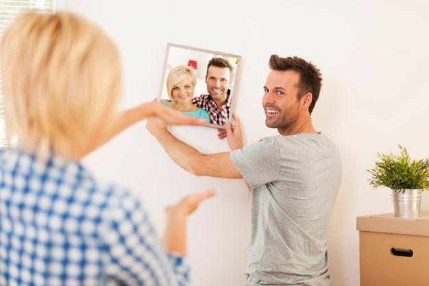 새로운 가정에서 벽에 프레임 사진을 거는 커플