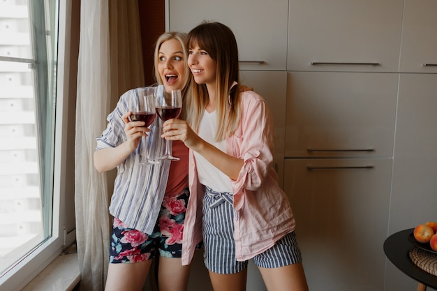 Couple of happy carefree women looking at window and holding glass of wine. cozy home atmosphere.
