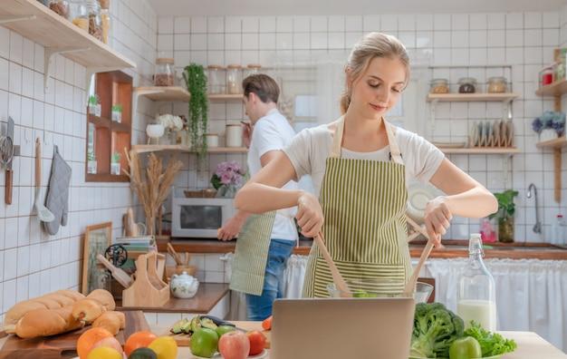 家庭の台所で朝の朝食に一緒にカップル幸せなサラダを調理