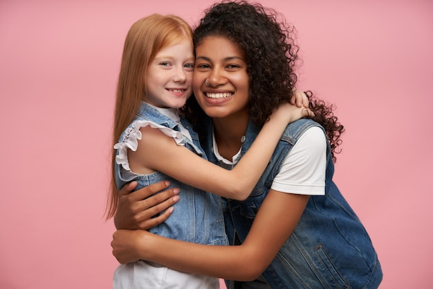 Couple of happy lovely young ladies in jeans vests and white shirts embracing each other lovingly and looking cheerfully with charming smiles, posing against pink