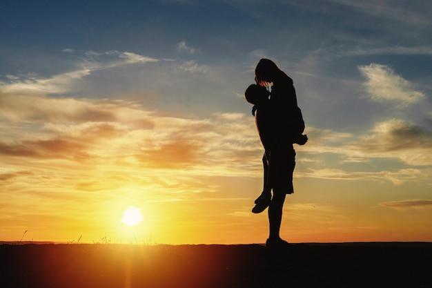 Пара счастлива на пляже закат романтический поцелуй силуэт