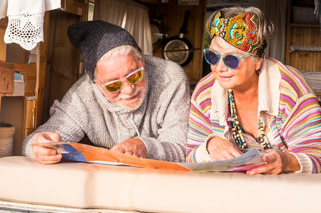 Couple of happy retired caucasian senior people enjoying travel and wanderlust lifestyle reading a map and planning the trip lay down inside an old vintage hand made customized van