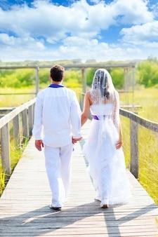 Couple happy in wedding day walking rear view