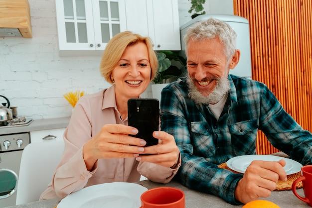 부부는 집에서 아침을 먹고 스마트 폰에서 뭔가를 읽습니다.