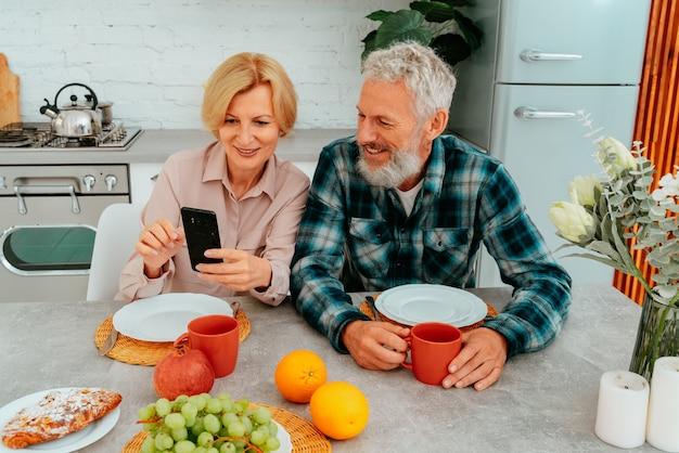 부부는 집에서 아침을 먹고 스마트폰으로 무언가를 읽는다
