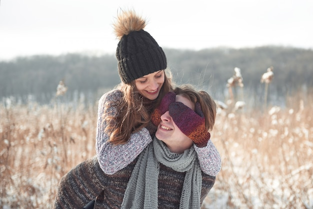 Couple has fun and laughs. kiss. young hipster couple hugging each other in winter park. winter love story, a beautiful stylish young couple. winter fashion  with boyfriend and girlfriend