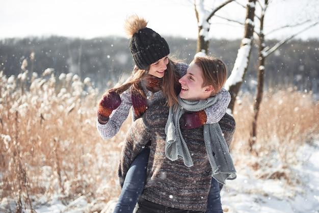 La coppia si diverte e ride. giovani coppie dei pantaloni a vita bassa che si abbracciano nel parco di inverno.