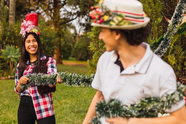 カップルはクリスマスの飾り付けを楽しんでいます。クリスマスの花輪で遊ぶ若いカップルの肖像画。