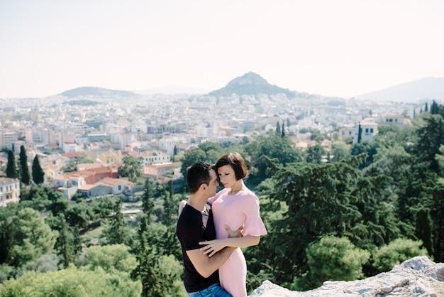 Пара встречается на вершине холма с панорамным видом на город, целует друг друга