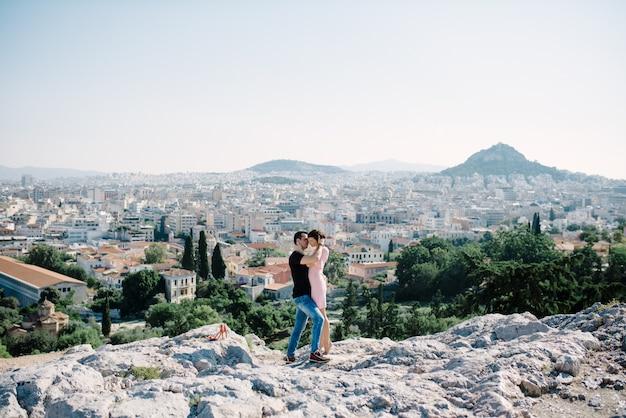 カップルは丘の頂上でデートし、街のパノラマビューでお互いにキスをする