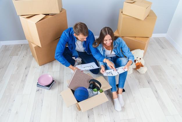 カップルは、多くの段ボール箱の間にある木製の床に座って、新しい家の設計について話し合います。新しく購入したフラットの家のデザインを計画する愛の美しい若いスタイリッシュなカップル。