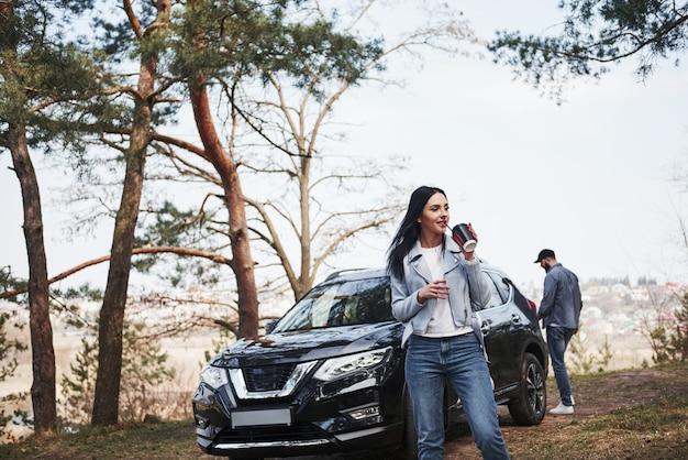 Couple have arrived to the forest on their brand new black car