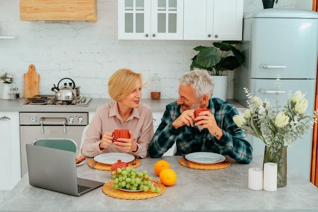 부부는 집에서 아침을 먹고 노트북으로 무언가를 본다
