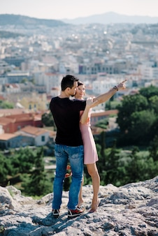 Couple have a date on the peak of the hill with panorama view on the city kissing each other