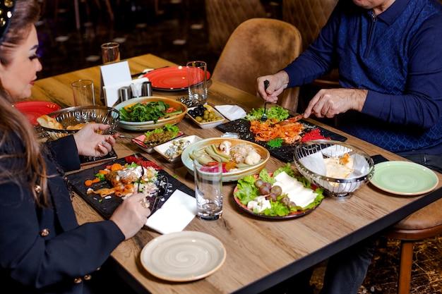 Пара обедает с пастой, салатами, сырной тарелкой, солеными огурцами и оливками