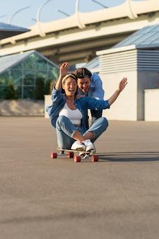 Couple have fun on longboard male push back of joyful female sitting on skateboard and laughing