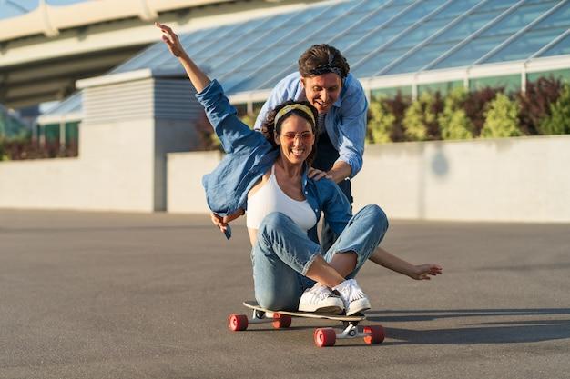 カップルはスケートボードに座って笑っている楽しい女性のロングボードの男性のプッシュバックを楽しんでいます