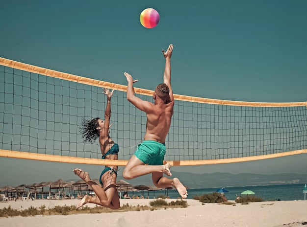 Couple have fun playing volleyball young sporty active couple beat off volley ball play game on summer day