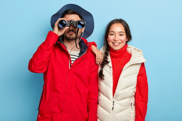 Couple have journey in mountains, look through binoculars, observe landscape, being full of energy, dressed in casual outfits, stand closely, isolated on blue