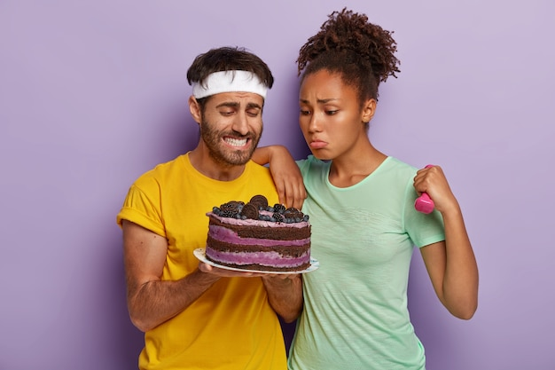 Couple have look at tasty sweet fruit cake, being hungry after exhausting training, woman holds dumbbell, dressed in casual clothes