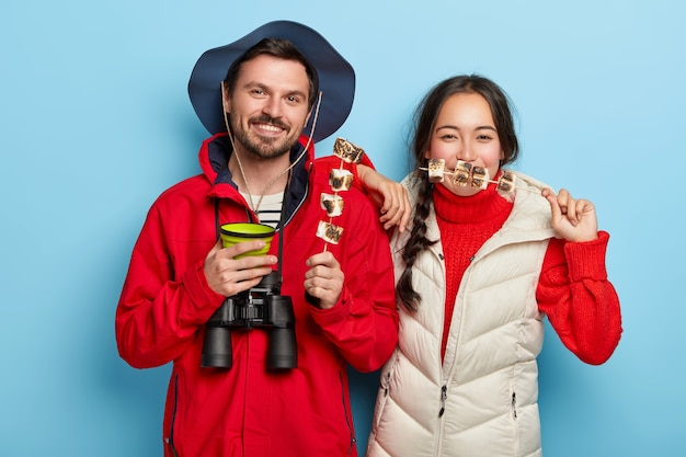 Couple have picnic together, enjoys being alone with nature, eat roasted marshmallow and drink coffee, being in good mood, pose against blue wall