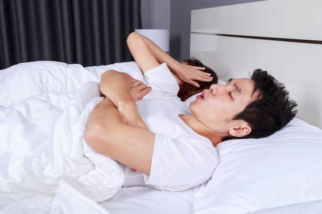 Couple have problem with man's snoring on bed