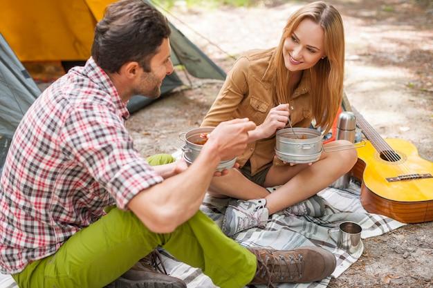 캠핑에서 맛있는 저녁 식사를하는 커플