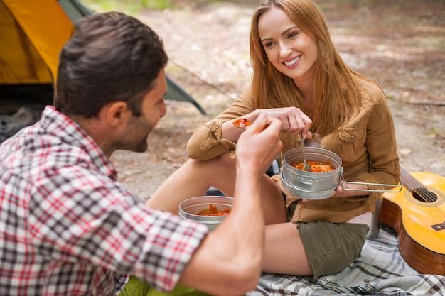 キャンプで美味しい夕食を食べているカップル