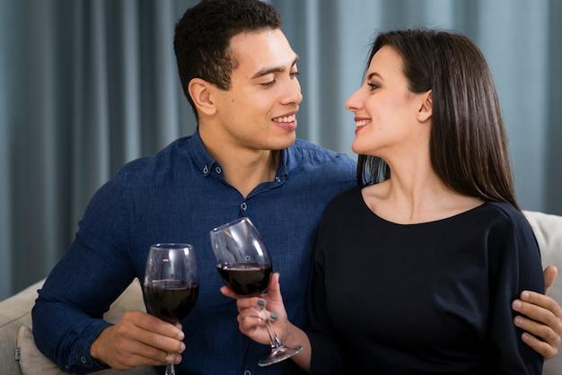Пара с бокалом вина, сидя на диване