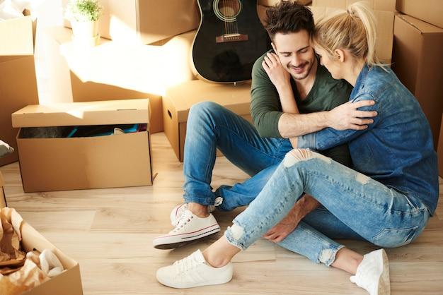 골판지 상자 사이에서 휴식을 취하는 커플