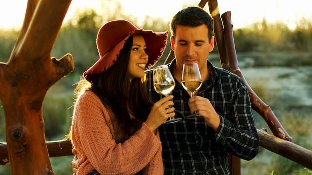 ロマンチックな瞬間を過ごし、美しい太陽フレアで白ワインを味わうカップル。