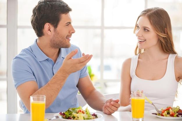 아침 식사를 하는 커플. 아침 식탁에 함께 앉아 이야기하는 아름다운 젊은 부부
